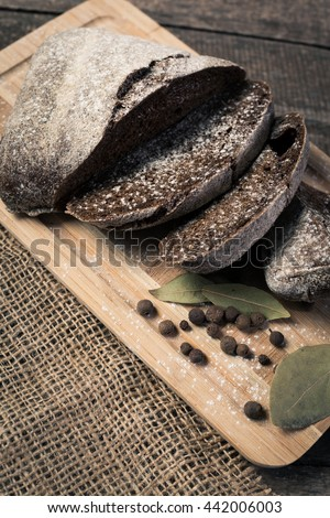 Tasty rustic bread on wooden table - stock photo