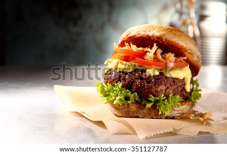 Tasty rustic iberico burger with a juicy meat patty, salad trimmings and mayo served on brown paper on a wooden counter, side view with copyspace - stock photo