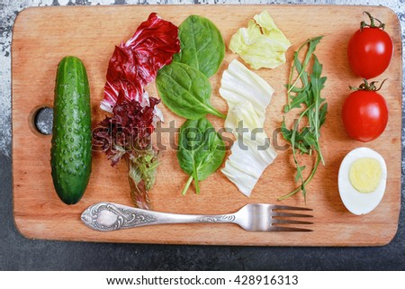 Tasty salad on the wooden board in the restaurant. Lettuce, cucumber, cabbage, tomato, egg on the chopping board next to the silver fork on the black table - stock photo