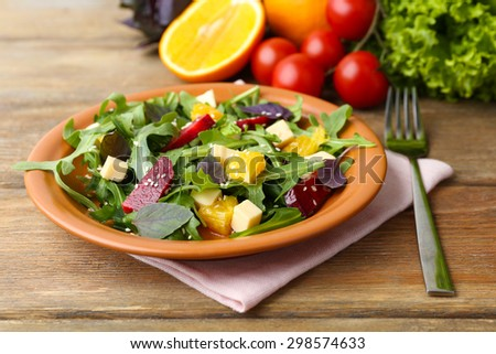 Tasty salad with arugula leaves in plate on wooden table, closeup - stock photo