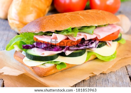 Tasty sandwich stuffed with ham,cheese and vegetables.selective focus on the sandwich - stock photo