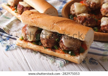 Tasty sandwich with meatballs and cheese close-up on the table. horizontal