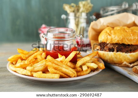 Tasty sandwiches and french fries on plate, on wooden background. Unhealthy food concept - stock photo