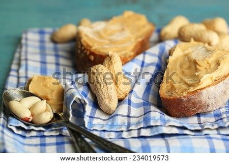 Tasty sandwiches with fresh peanut butter on wooden background - stock photo