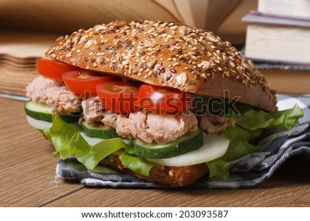 Tasty school lunch: a sandwich with tuna and vegetables closeup on background books on the table. horizontal   - stock photo