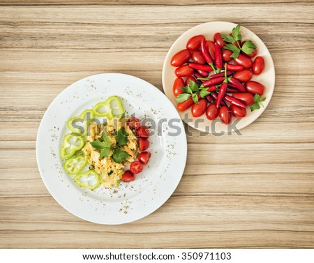 Tasty scrambled eggs with paprika, cherry tomatoes, chili peppers and celery leaves. Rich breakfast. View from above. - stock photo