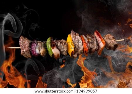 Tasty skewers with fire flames, close-up. - stock photo