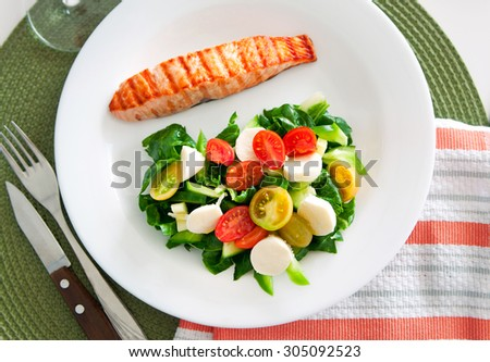 Tasty slice of fried salmon served with mix salad of kale leaves, cherry tomatoes and bocconcini cut in halves, cucumber, served on a white plate. Healthy food. Selective focus, top view, copy space - stock photo