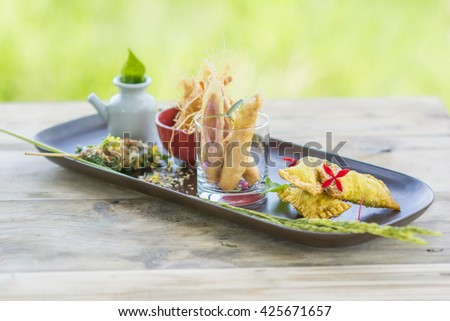 Tasty snack in fusion style : Ham wrapped fried dumplings, Prawn fried rice noodles, Roast beef wrap Piper sarmentosum leaves. - stock photo