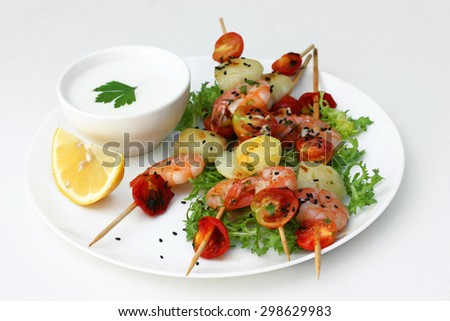 Tasty snack in fusion style: shrimp, potatoes and tomatoes in a bowl isolated on white background - stock photo