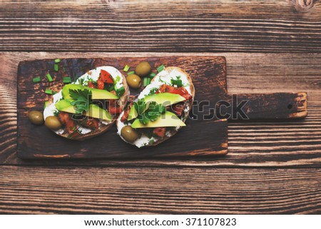 Tasty snack of open sandwich with avocado and soft cheese on wooden cutting board. Top view - stock photo