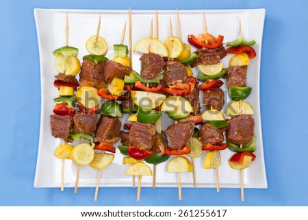 Tasty spicy marinated meat and vegetable kebabs displayed on a platter on their skewers ready for the summer barbecue, overhead view on a blue background - stock photo