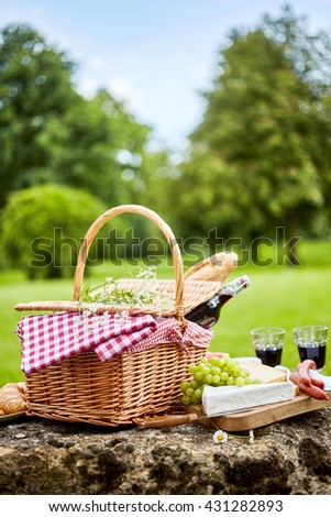 Tasty spring picnic lunch with red wine, baguette, assorted cheese, grapes and spicy sausages with a wicker hamper and checked cloth on a rock in a park - stock photo