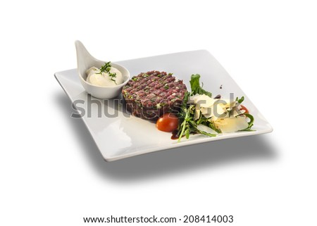 Tasty Steak tartar and rocket salad with cheese ready to serve isolated on white plate - stock photo