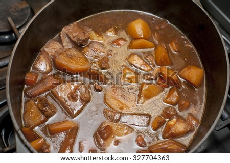 Tasty stew or hot pot with cubed lamb or beef in a rich gravy with carrots and potatoes, viewed from above in a pot ready for serving - stock photo
