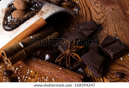 tasty still - heap of  coconut flakes, chocolate, sticks of cinnamon and anise, and white modern plate with brown ball candy on wooden table - stock photo