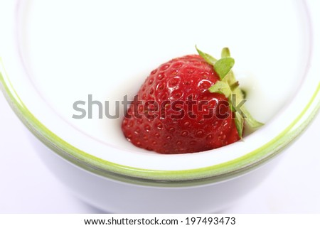 tasty strawberry into a cup of white yogurt - stock photo