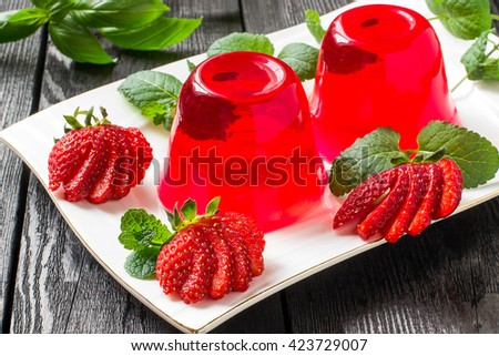 Tasty strawberry jelly and ripe strawberries on plate on a dark wooden table. Selective focus - stock photo