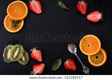 tasty summer fruits on a black table. Cherry, strawberries,oranges, kiwi - stock photo