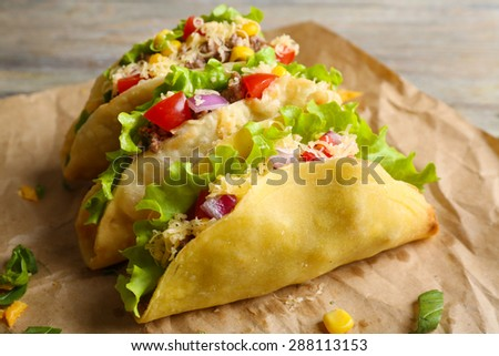 Tasty taco with greens on paper close up - stock photo
