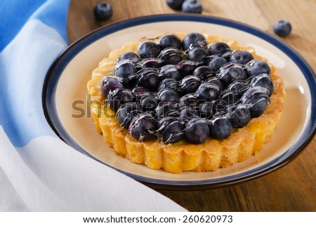 Tasty tart with blueberries  on wooden table. - stock photo