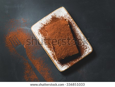 Tasty tiramisu cake on black background, top view