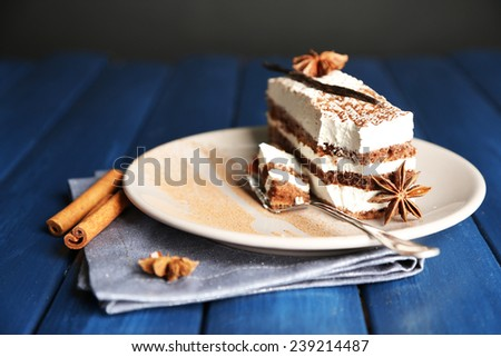 Tasty tiramisu cake on plate, on wooden table, on black background - stock photo