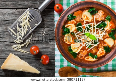 tasty tortellini tomato soup  in a clay rustic bowl decorated with basil leaves, on an old table with piece of parmesan cheese and a grater, top view - stock photo