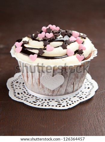 Tasty vanilla cupcake decorated with pink hearts on a old brown background - stock photo