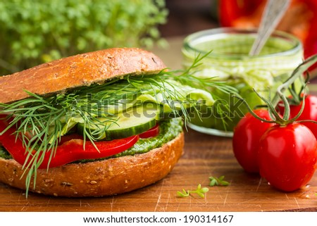 Tasty vegan wholemeal bagel with green pesto, fresh vegetables and dill. Selective focus. - stock photo