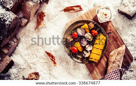 Tasty vegetarian or vegan winter fare with grilled veggie kebabs and corn on the cob on a vintage pewter plate served outdoors in the snow with bread and a savory dip, overhead view - stock photo