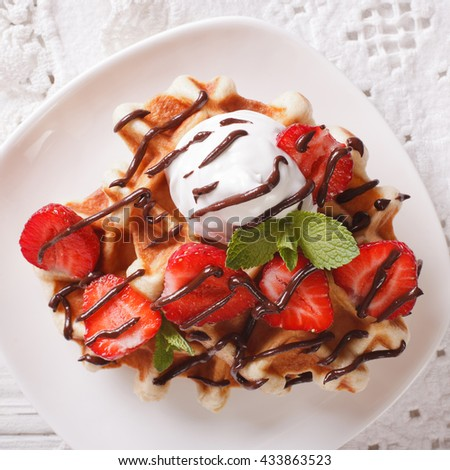 Tasty waffles with strawberries, whipped cream and chocolate frosting close up. horizontal view from above