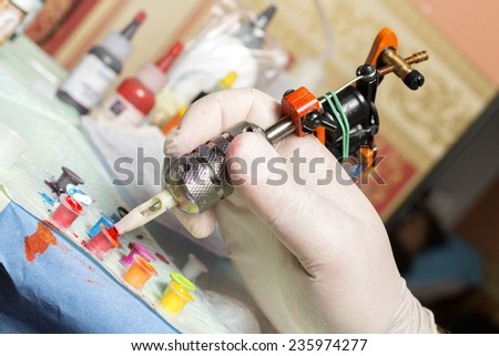 Tattoo artist at work. Closeup - stock photo