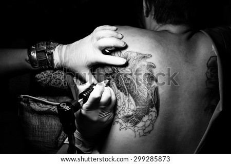 Tattoo artists are tattooing women clients black background. Decoration Art Machine Making Process Studio Man Female Lifestyle Body Action Designs Ink Master Gun Concept Skin People Free Artwork Draws - stock photo