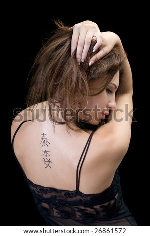 Tattoo on a back of the young woman - stock photo