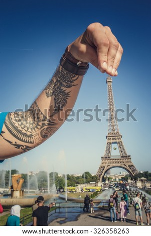 Tattooed arm abover eifel tower over blue sky. - stock photo