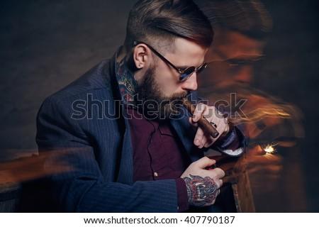 Tattooed bearded man in sunglasses smoking a cigar. - stock photo
