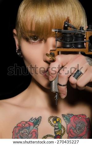 tattooed beautiful woman with tattoo machine, dark background - stock photo