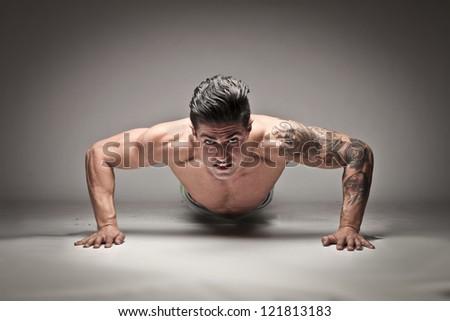 Tattooed man doing push ups - stock photo