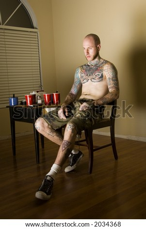 tattooed man watching TV - stock photo