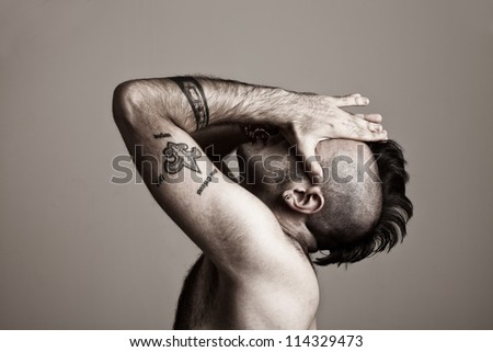 tattooed young man suffering.his hands on his face. - stock photo