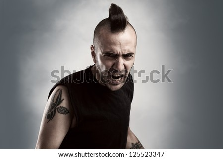 tattooed young man with mohawk style hair screaming - stock photo