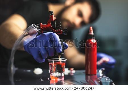 Tattooist makes a tattoo. Closeup - stock photo