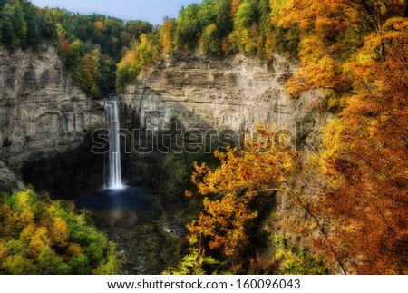 Taughannock Falls is  located in Ulysses,Y New York. Photo taken from an overlook during fall. A gorgeous 215 foot waterfall found in the Finger Lakes region. - stock photo