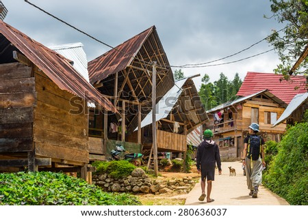 Taupe, Indonesia - August 16, 2014: Backpacker visiting the traditional village of Loko in the hilly region of Mamasa, West Tana Toraja, remote but upgrowing travel destination in Sulawesi, Indonesia. - stock photo