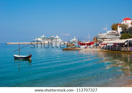 Taverns with red boat in the port of the Greek island against a cruise ship. Mykonos. - stock photo
