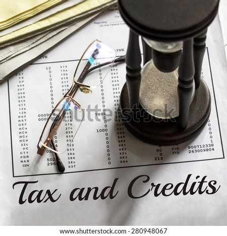 Tax and credits concept. Getting refund from the income tax return. Hourglass on financial documents in the background. - stock photo