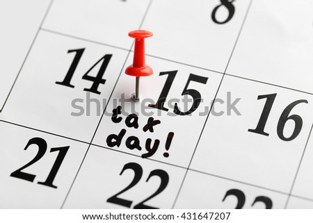Tax day written and pinned in a calender on date of 15th, close up - stock photo