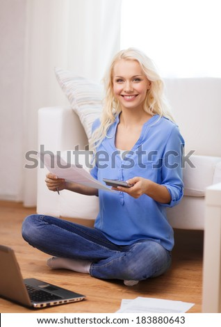 tax, finances, technology, home and happiness concept - smiling young woman with papers, laptop computer and calculator at home - stock photo