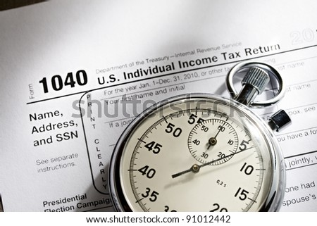 Tax form and stopwatch - stock photo